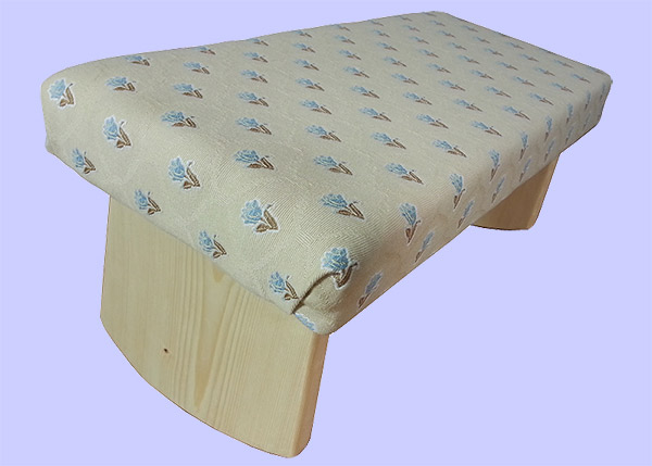 a meditation bench covered in tan fabric with a blue flower design