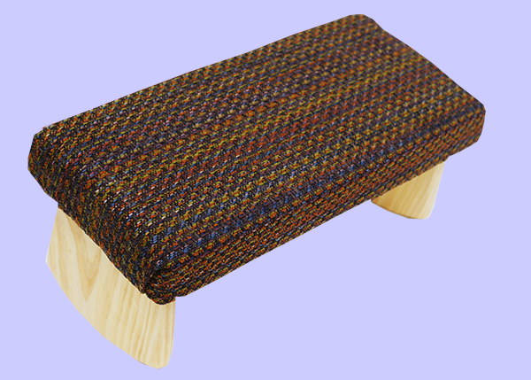 meditation bench with orange, green, brown and blue woven fabric